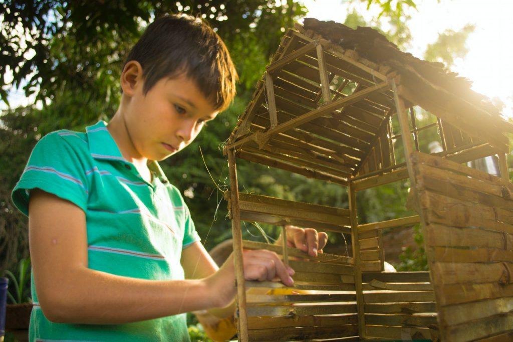 Petit garçon fabricant une cabane en bois