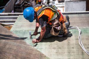 Homme isolant une toiture en sécurité