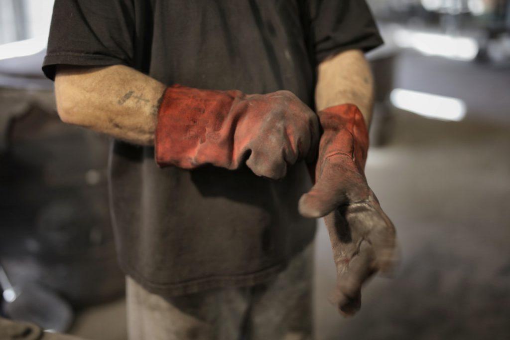 Homme mettant ses gants de protection pour bricoler