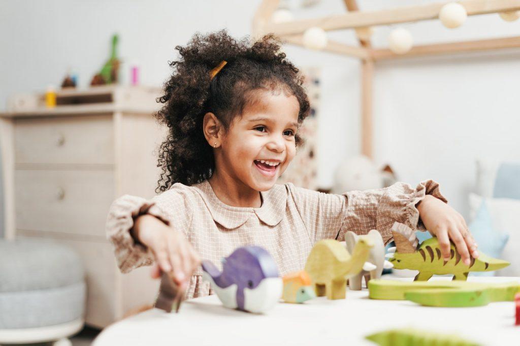 Petite fille heureuse, jouant avec des figurines en forme d'animaux