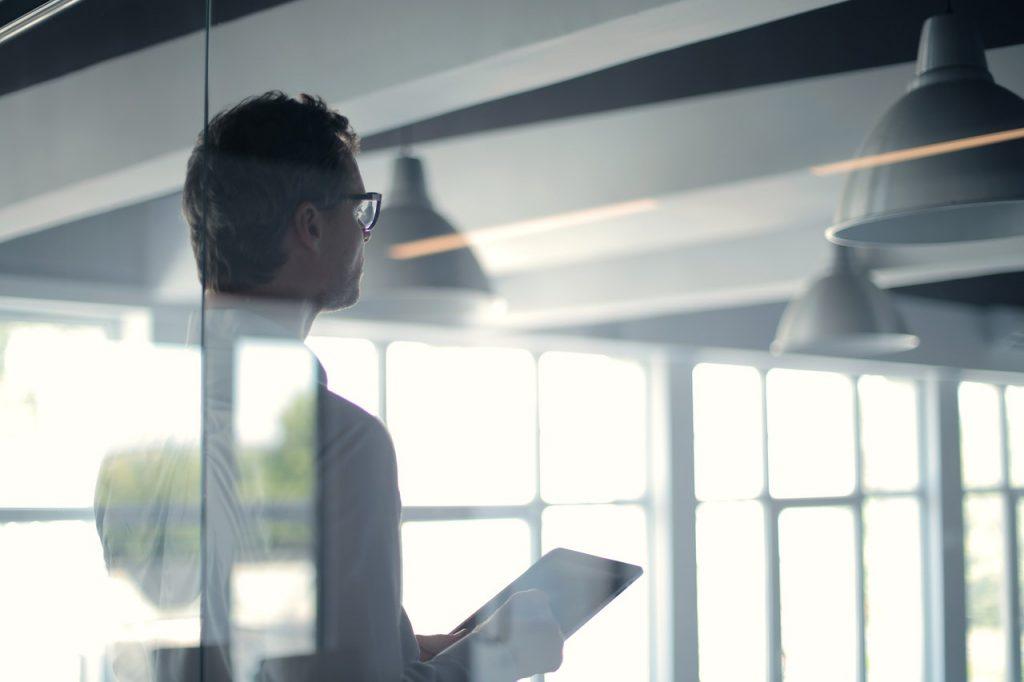 Homme dans un bureau vitrée, dans une entreprise, durant une réunion