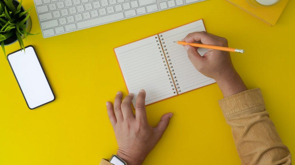 homme travaillant sur un bureau jaune