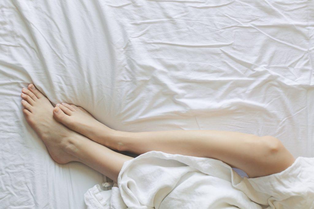 Femme allongée sur un matelas avec une couette pied à l'air
