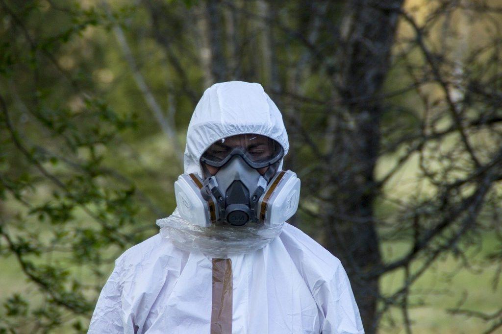 Homme recouvert d'une blouse de la tête au pieds, avec masque respiratoire