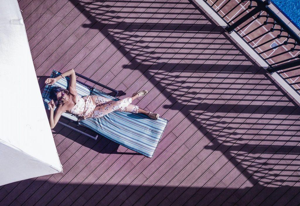 Femme allongée sur une chaise longue, sur une terrasse ensoleillée en bois composite