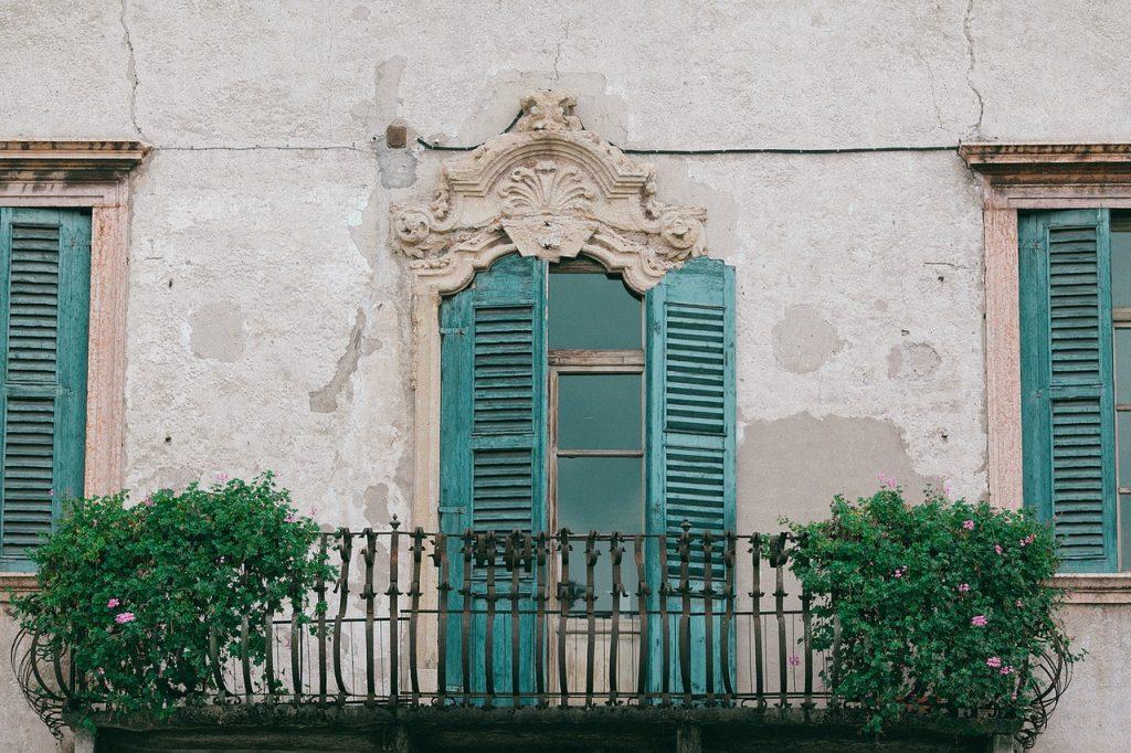 Balcon en fer forgé, fenêtre avec volet battant ajouré bleu