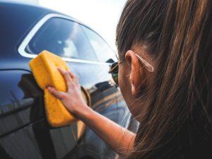 Femme nettoyant carrosserie avec grosse éponge orange