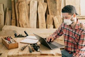 Homme sur un chantier menuisier, devant son ordinateur